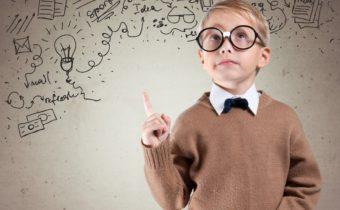 Kid. Portrait of male elementary school student with lightbulb picture on blackboard